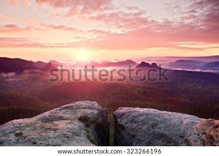 View over sandstone cliff into deep misty valley in Saxony Switzerland. Sandstone peaks increased from foggy background, the fog is orange due to sunrise. - stock photo