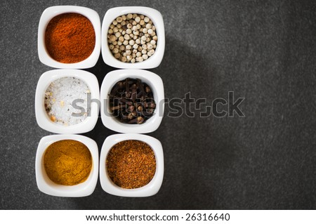 view over several colorful pots with spices. grey background. gourmet cooking. - stock photo