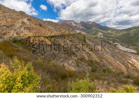 View over the lunar landscape around Queenstown, Tasmania, Australia. The road out of Queenstown to Hobart goes up Mount Lyell. Here you get to see just how damaged the land really is. - stock photo