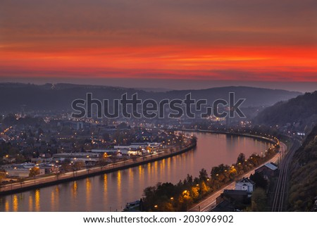 View over the Meuse to Huy in Belgium during a fiery red sunset - stock photo
