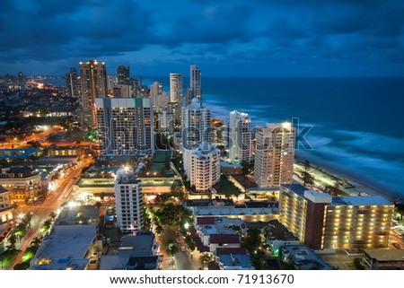 view over the modern city at dusk with ocean beside (gold coast,qld,australia) - stock photo