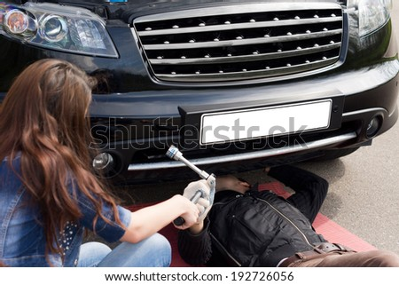 View over the shoulder of a female driver of a mechanic working on a roadside breakdown as she hands him his tools underneath the car - stock photo