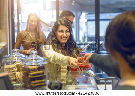 View over the shoulder of the cashier of an attractive young blond woman making payment at a till looking in her purse - stock photo