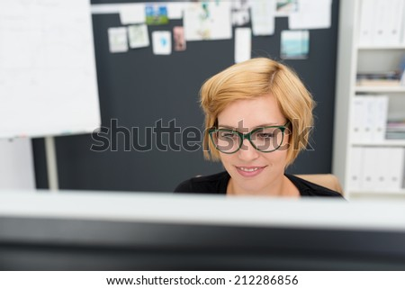 View over the top of the desktop monitor of a young businesswoman at work in the office concentrating on information on the screen - stock photo