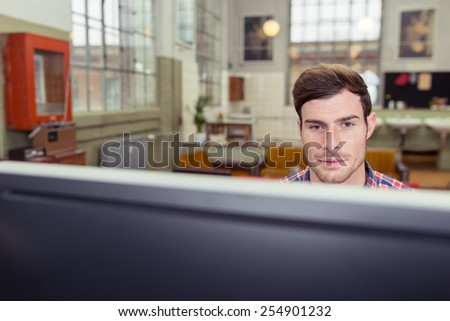 View over the top of the monitor of a handsome young man sitting working at a computer in a large spacious room with focus to his face - stock photo