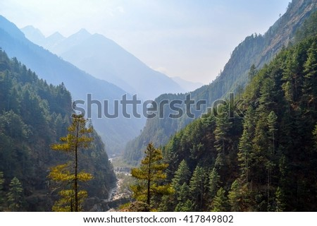 View over trees and Himalayan mountains, Nepal - stock photo