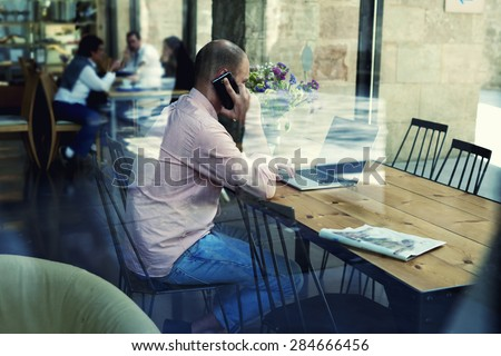 View though window, young businessman using laptop computer and smart phone while working busy, male student or freelancer working on notebook at wooden table of modern coffee shop, glassy reflection - stock photo