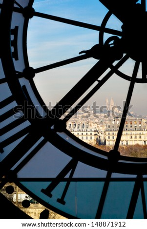 View through a D'orsay clock tower of Sacre-Coeur Basilica on the hilltop in Paris France - stock photo