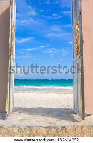 View through a door of a beautiful tropical beach - stock photo