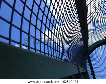 View through a enclosed train overpass walkway into the cloudy blue skies. - stock photo