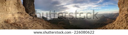 View through a frame of rocky mountain cliffs of the sunrise over distant mountain ranges and valleys as the sun peeks over the horizon - stock photo