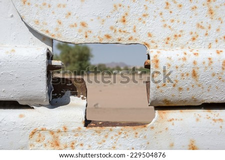 view through a hole in the US border fence from Mexico to the United States with the focus on the fence - stock photo