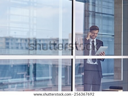 View through a window of a corporate executive talking on his phone and looking at a digital tablet - stock photo