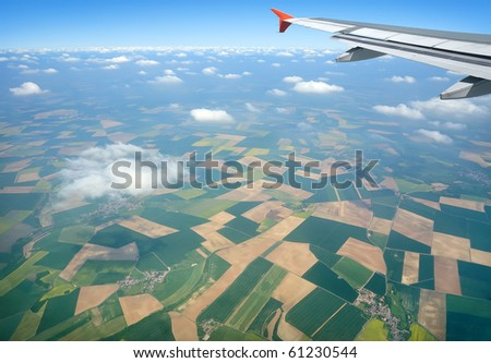 View through airplane porthole with cultivated fields, blue sky, light clouds and part of airplane wing