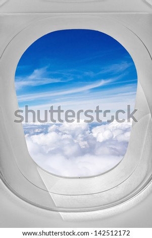 View through airplane window, sky over the clouds - stock photo