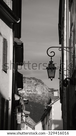 View through the narrow medieval street on the mountains at background during sunset (Annecy, France). A game of  contrasting light and shadow. Aged photo.