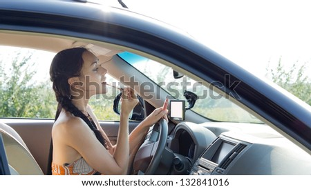 View through the side window of a female driver applying make-up using the rear view mirror in the car