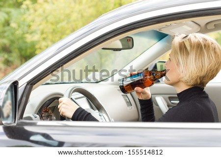 View through the side window of a woman driving along in her car drinking alcohol from the bottle and posing a threat to other motorists - stock photo