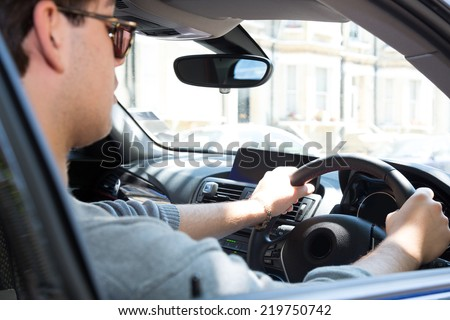View through the side window of a young man driving a car in an urban environment - stock photo