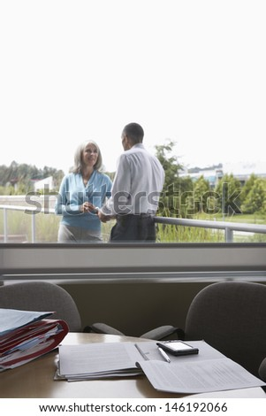View through window of business couple talking on terrace - stock photo