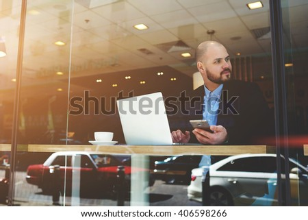 View through window of male skilled managing director with net-book and mobile phone in hands is waiting client for a planned meeting in cafe. Young businessman is using cell phone and laptop computer - stock photo