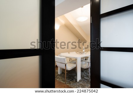 View to a dining room through the opened door - stock photo
