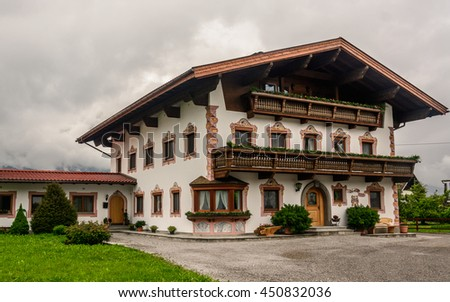 View to a typical traditional austrian house with a wooden roof, brown door, windows with two shutters, and long balcony. Walls are decorated pictures on stucco - dark clouds in the background - stock photo