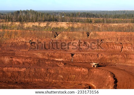 View to an open mine wall and few yellow tip-trucks - stock photo