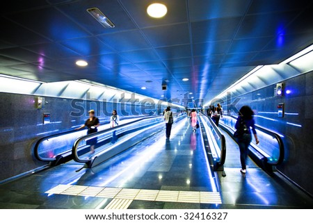 View to blue corridor with escalators and people going on it - stock photo