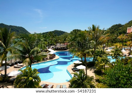 View to swimming pool and houses of tropical resort. - stock photo