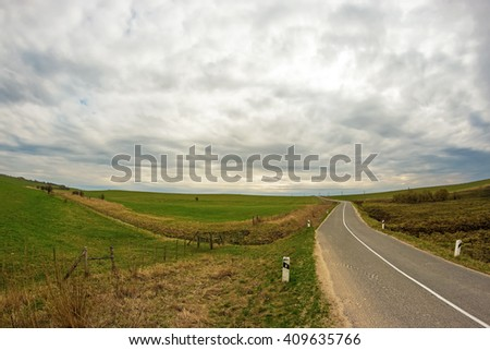 View to the curvy road among green meadows - stock photo