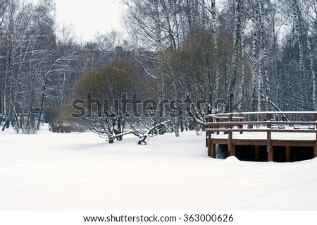 View to wooden railings from frozen river with a lot of snow