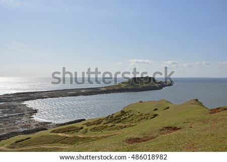 View to Worms Head or Penrhyn-gwyr on the Gower Peninsular at Rhossili in Wales, United Kingdom. With people walking on beach at low tide