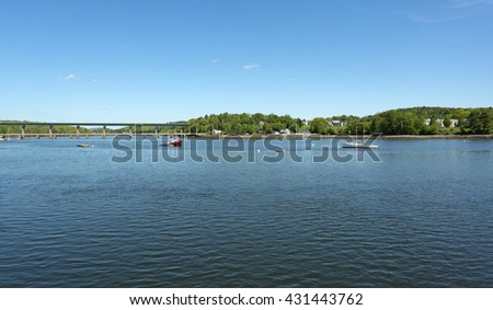 View two lobster boats moored at Belfast, Maine in the early spring with a footbridge and a traffic bridge in the distance. - stock photo