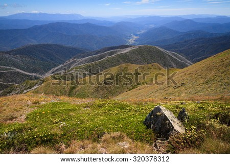 View west towards Ovens Valley from Mt Feathertop, Victoria, Australia. Taken In summer, with masses of wildflowers in the foreground. - stock photo