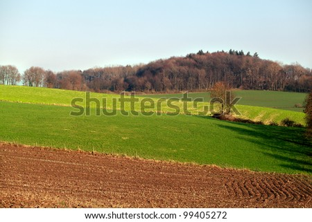 view with pastures and plowed field on the hills - stock photo