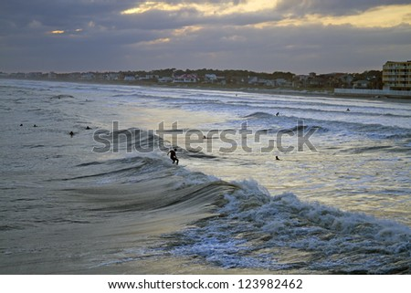 Viewed from the sea, surfers surf turbulent waves at sunset at Folly Beach, South Carolina shortly before Hurricane Sandy hits - stock photo