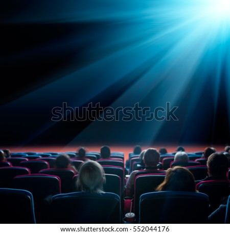 viewers watch shining star at cinema, long exposure, blue glow