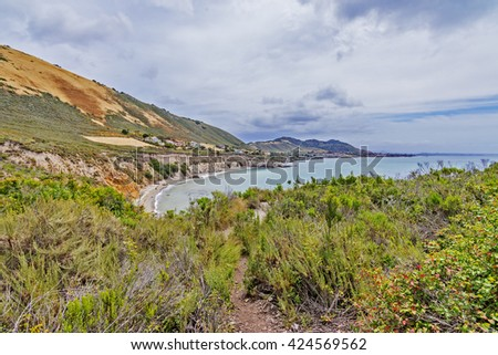Viewing Pirate's Cove with shimmering aquamarine sea, puffy clouds, & waves crashing on a rocky beach, along steep sheer jagged cliffs, California Central Coast, photographed near Avila Beach CA. - stock photo