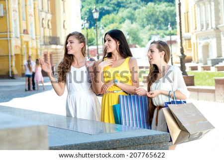 Viewing storefront of the shop. Three attractive young girl holding shopping bags while standing outdoors laughing and smiling and holding hands - stock photo