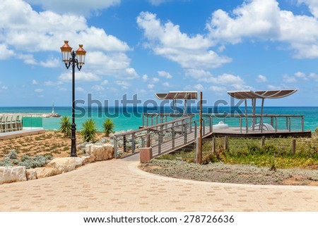 Viewpoint and lamppost on promenade overlooking Mediterranean sea under blue sky with white clouds in Ashqelon, Israel. - stock photo