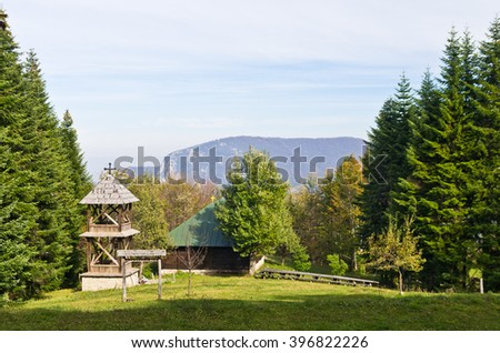 Viewpoint on a landscape of mount Bobija, meadow in front of an old wooden church surrounded by tall fir trees with rocky peaks in backgound, west Serbia - stock photo