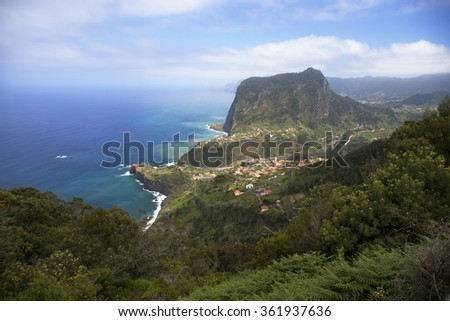 Viewpoint on the coastal road overloooking the Eagle Rock Mountain next to the village of Faial surrounded by fertile terraces, vineyards, orchards and forests on north coast of Madeira - stock photo
