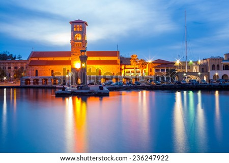 Views across the entrance to Mandraki Harbour Rhodes Greece with Evangelismos Church in the background. - stock photo