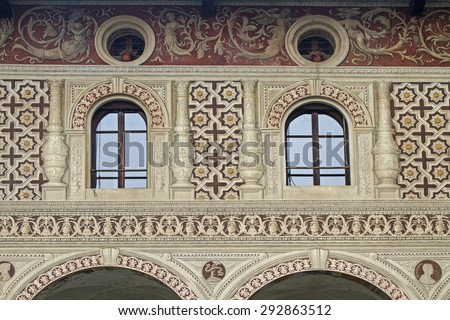 Vigevano - Detail view of a Renaissance palace with sand-colored facades and eggplant-colored paintings - stock photo