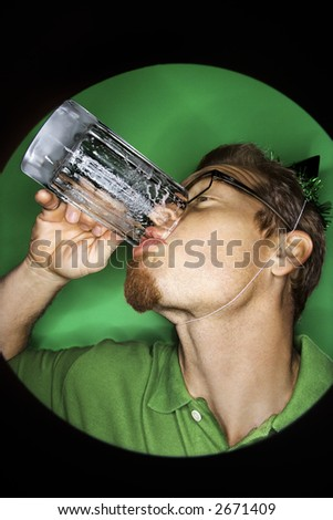 Vignette of adult Caucasian man on green background wearing green hat and drinking beer. - stock photo
