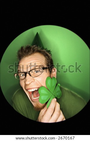 Vignette of excited adult Caucasian man on green background wearing Saint Patricks Day hat and holding shamrock. - stock photo
