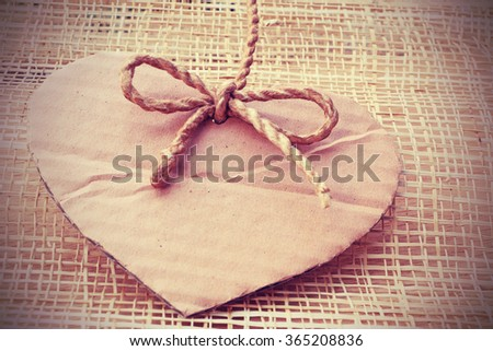 Vignette Style, Series of Valentines Card, Heart Shape Blank Cardboard with Flax Cord hanging on wooden weaving background. Photoshop Vintage Effect. - stock photo