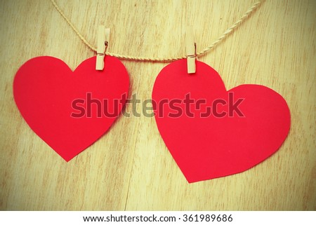 Vignette Style, Series of Valentines Card. Red heart paper cut with clothes pin on wooden background, in very shallow focus. Image of Valentines day. - stock photo