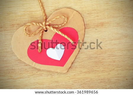 Vignette Style, Series of Valentines Card, Three Heart Shape Blank Cardboard with Flax Cord hanging over wood background. - stock photo